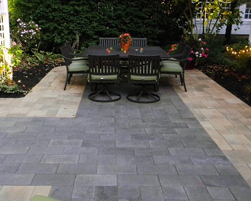 Custom Paver Patio Surrounded by Landscaping and Lighting
