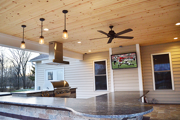 Covered Outdoor Kitchen with TV and Circular Bar